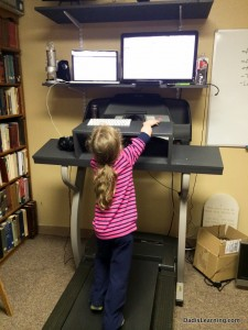 Our daughter enjoying a stroll and a show on my DIY treadmill desk.